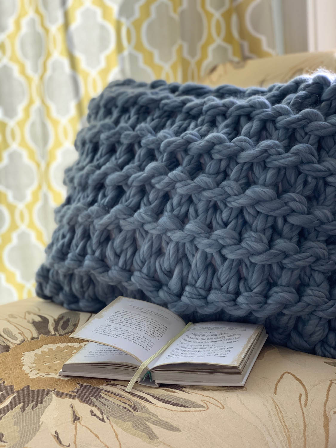 Hand knit pillow in garter stitch using jumbo yarn on cushion with book