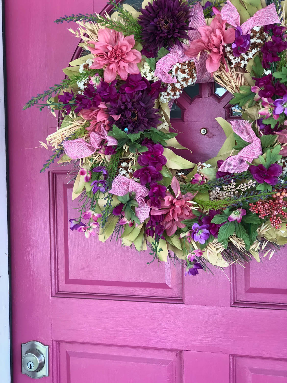 finished DIY upcycled spring wreath with silk flowers on pink front door