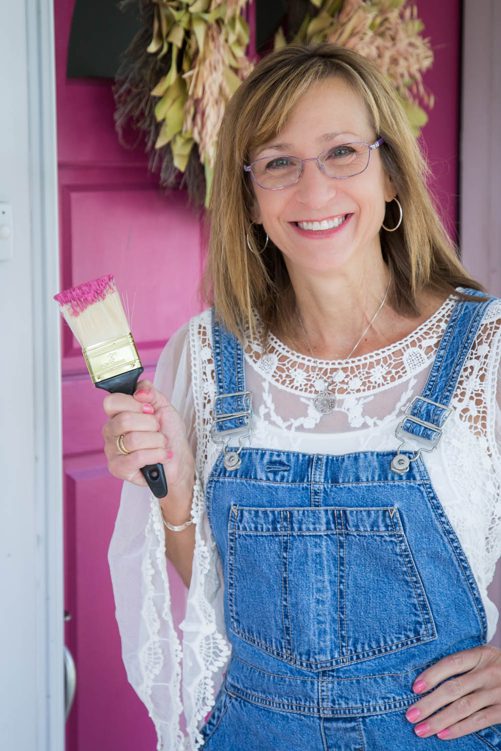 Ashley Quinn in front of pink door with paintbrush