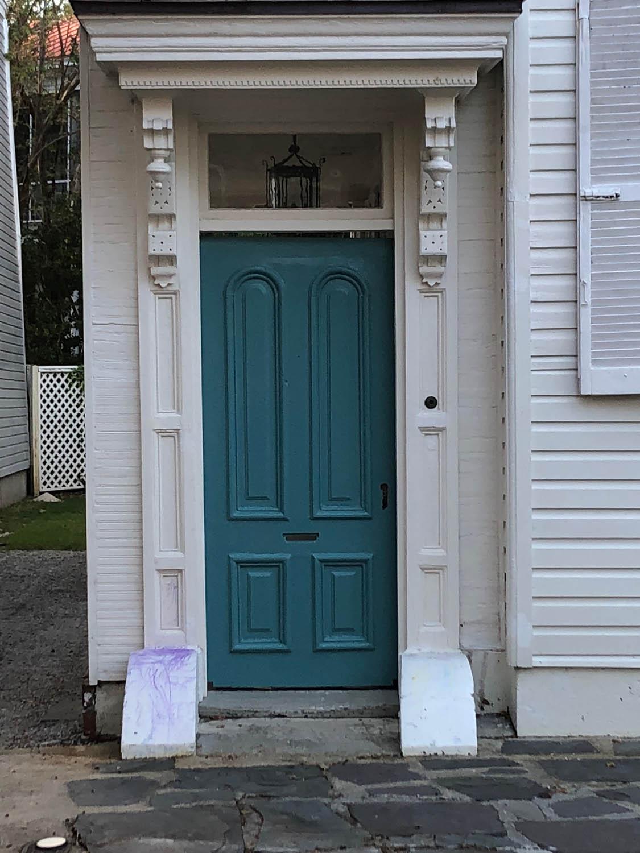 green exterior door with beautiful woodwork trim