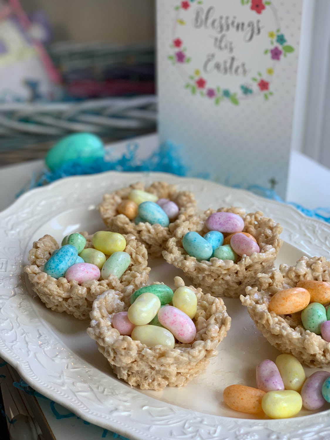 Rice Crispy Treat recipe shaped into nests filled with jelly beans displayed on a white plate with an Easter card