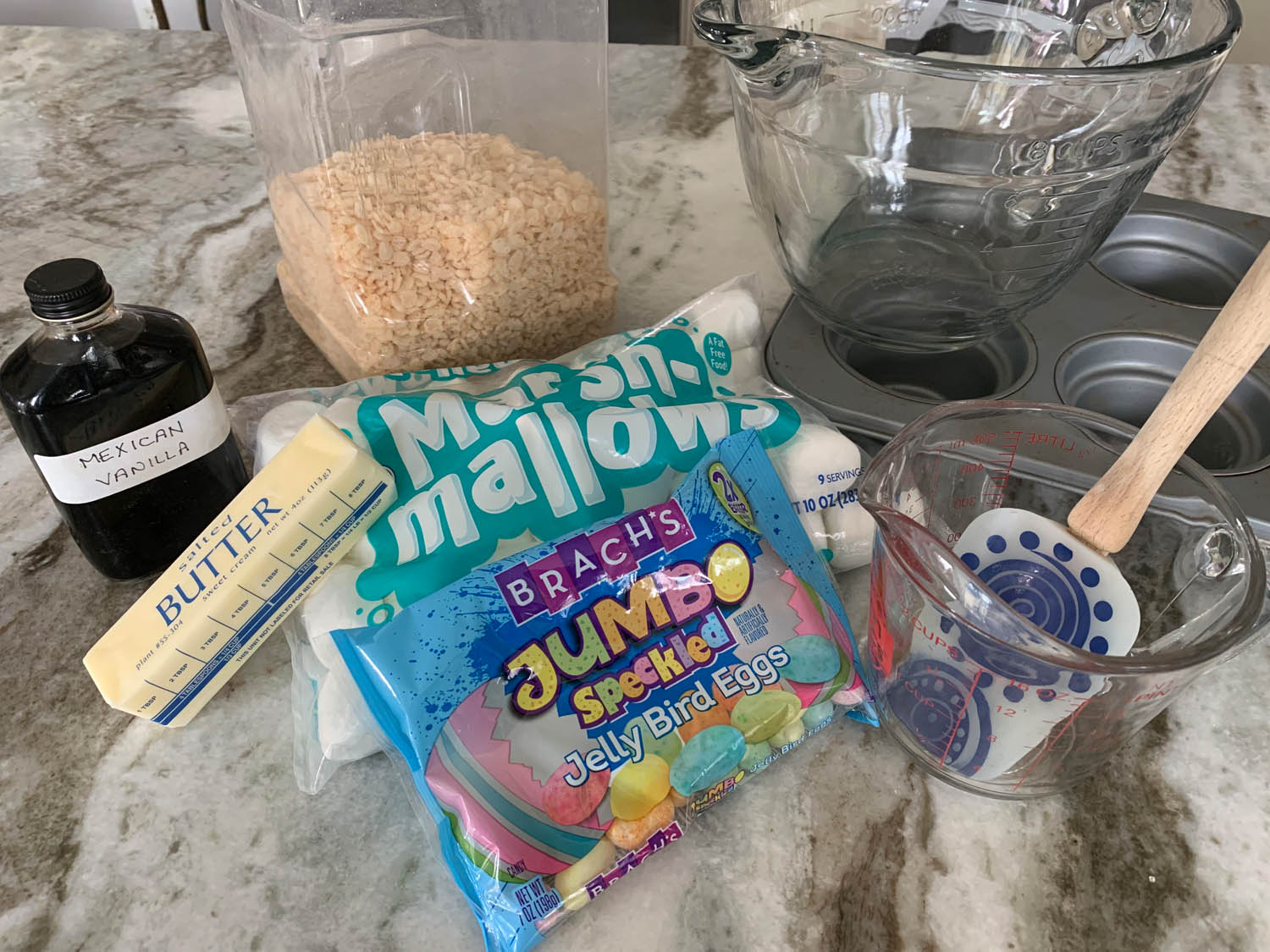 vanilla, Rice Crispies cereal, butter, marshmallows, measuring cups, muffin tin, and jelly bird eggs ingredients for Easter Nests made from Rice Crispy Treats
