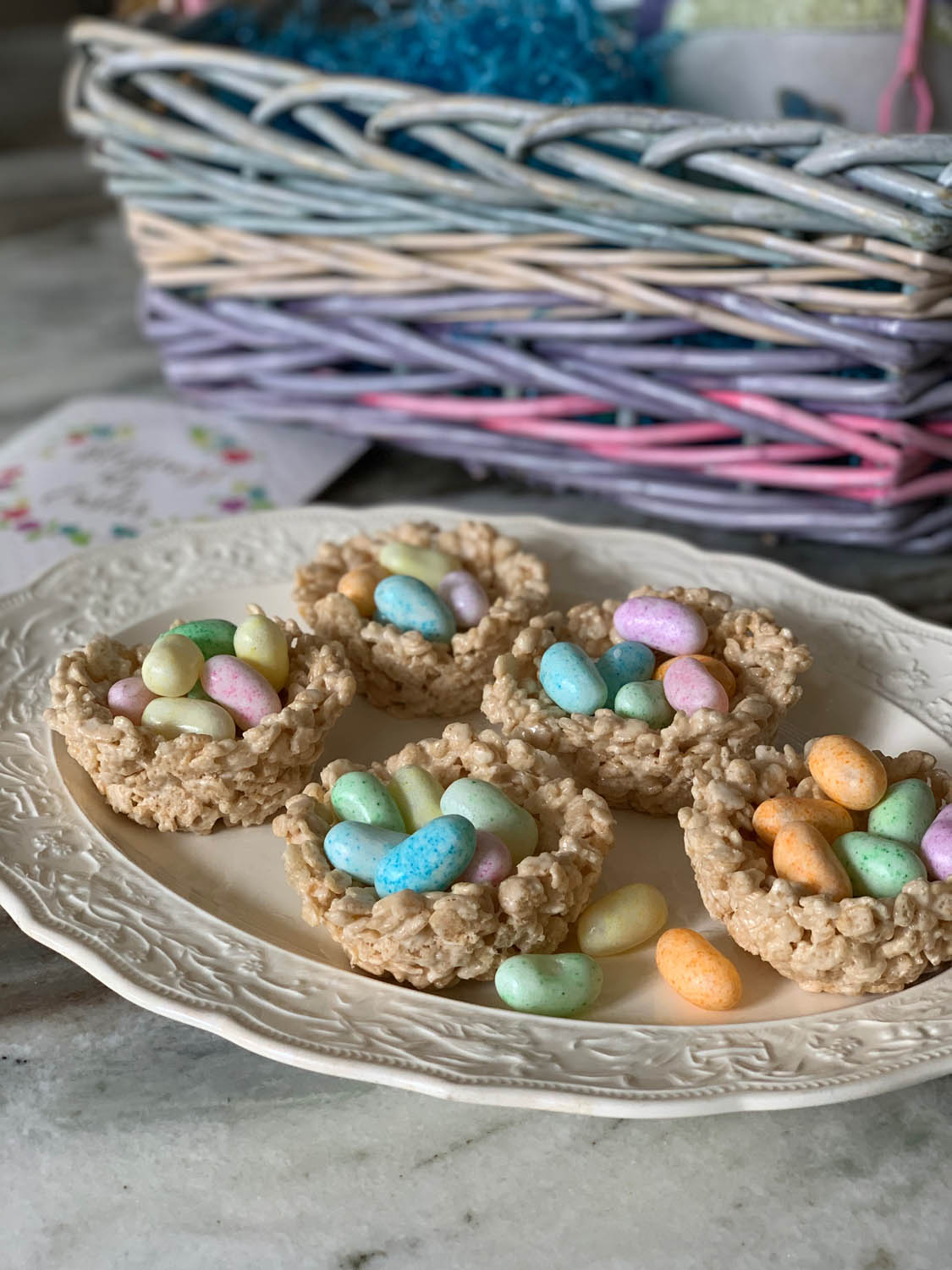 finished Rice Crispy Treats Easter Nests filled with jelly beans and displayed on a white platter next to a rainbow Easter basket