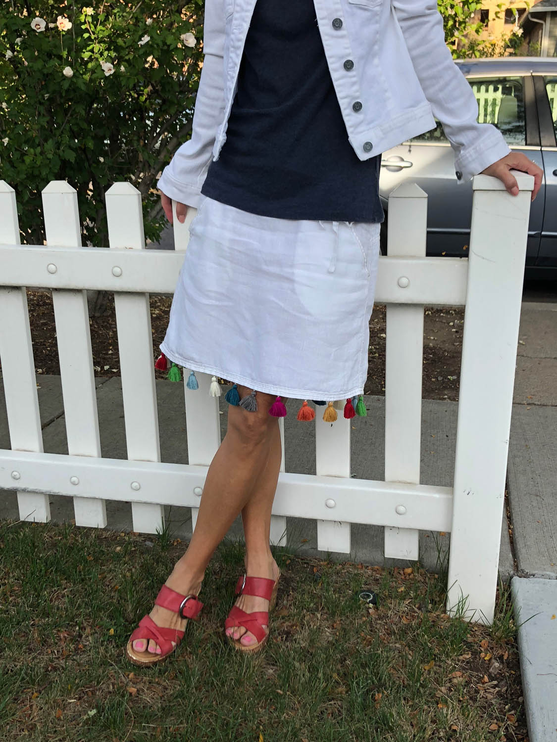 woman modeling finished white linen skirt with multicolor tassel trim embellishment