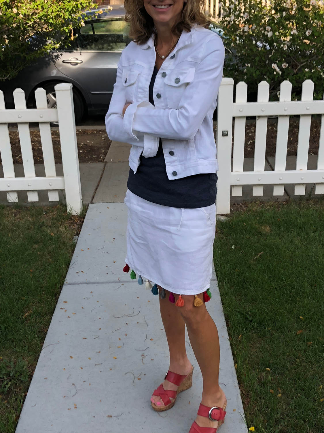 Woman modeling finished white linen skirt embellished with colorful purchased tassel trim.