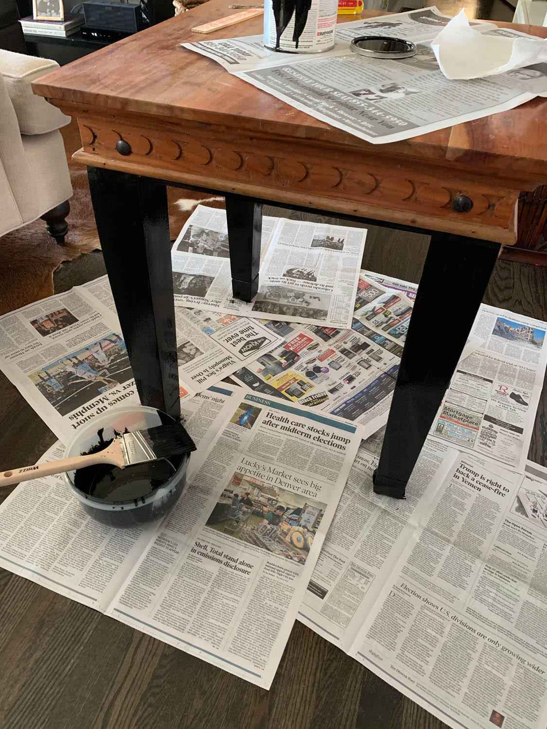old end table on top of newspapers with bowl of homemade chalk paint and paint brush