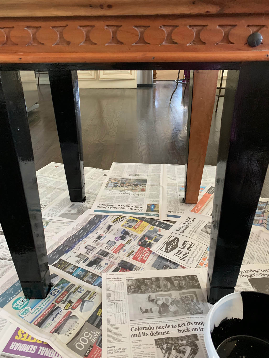 thrifty end table on top of newspapers with legs in process of being painted