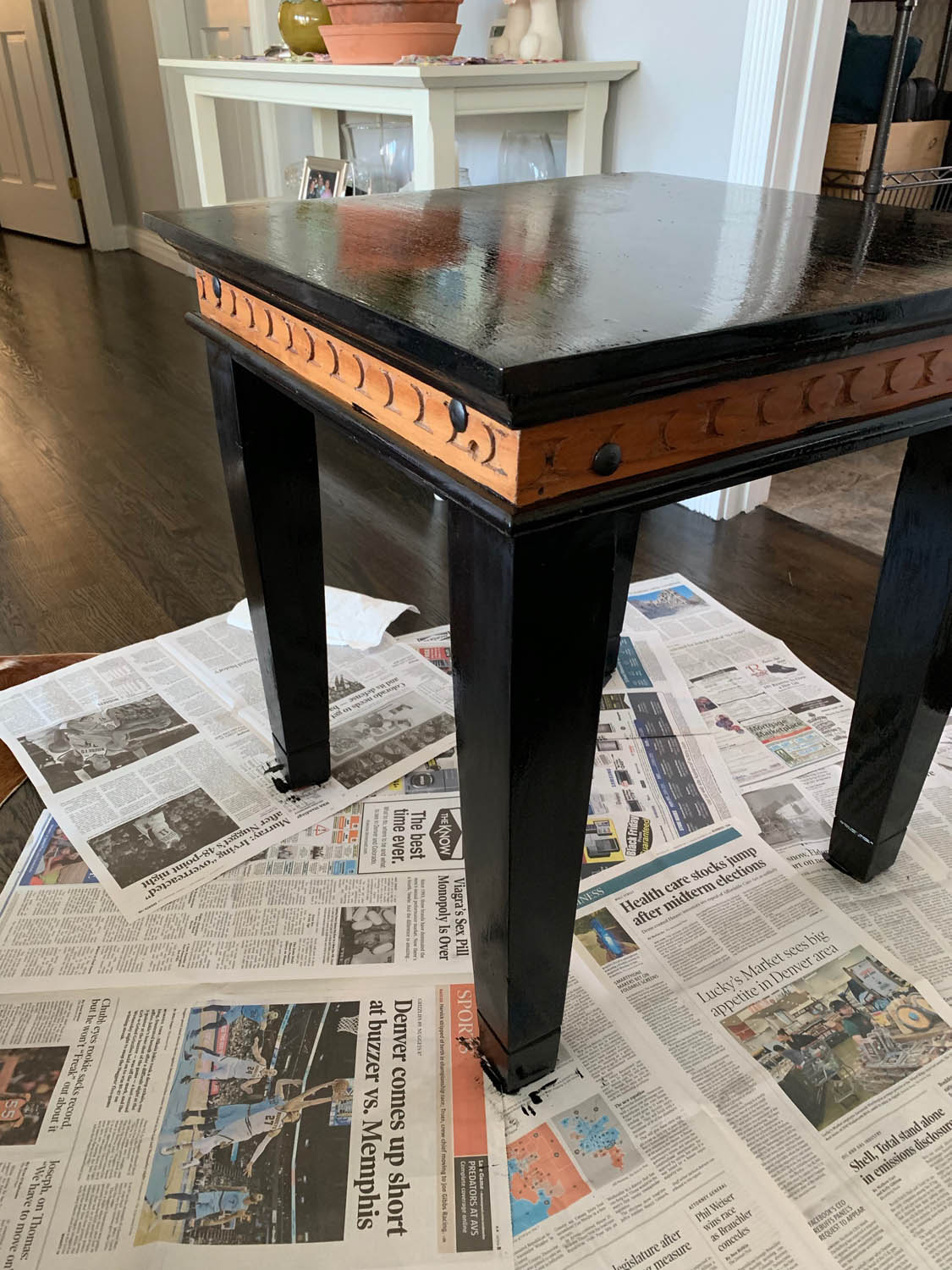 end table on newspapers with homemade chalk paint almost covering the table