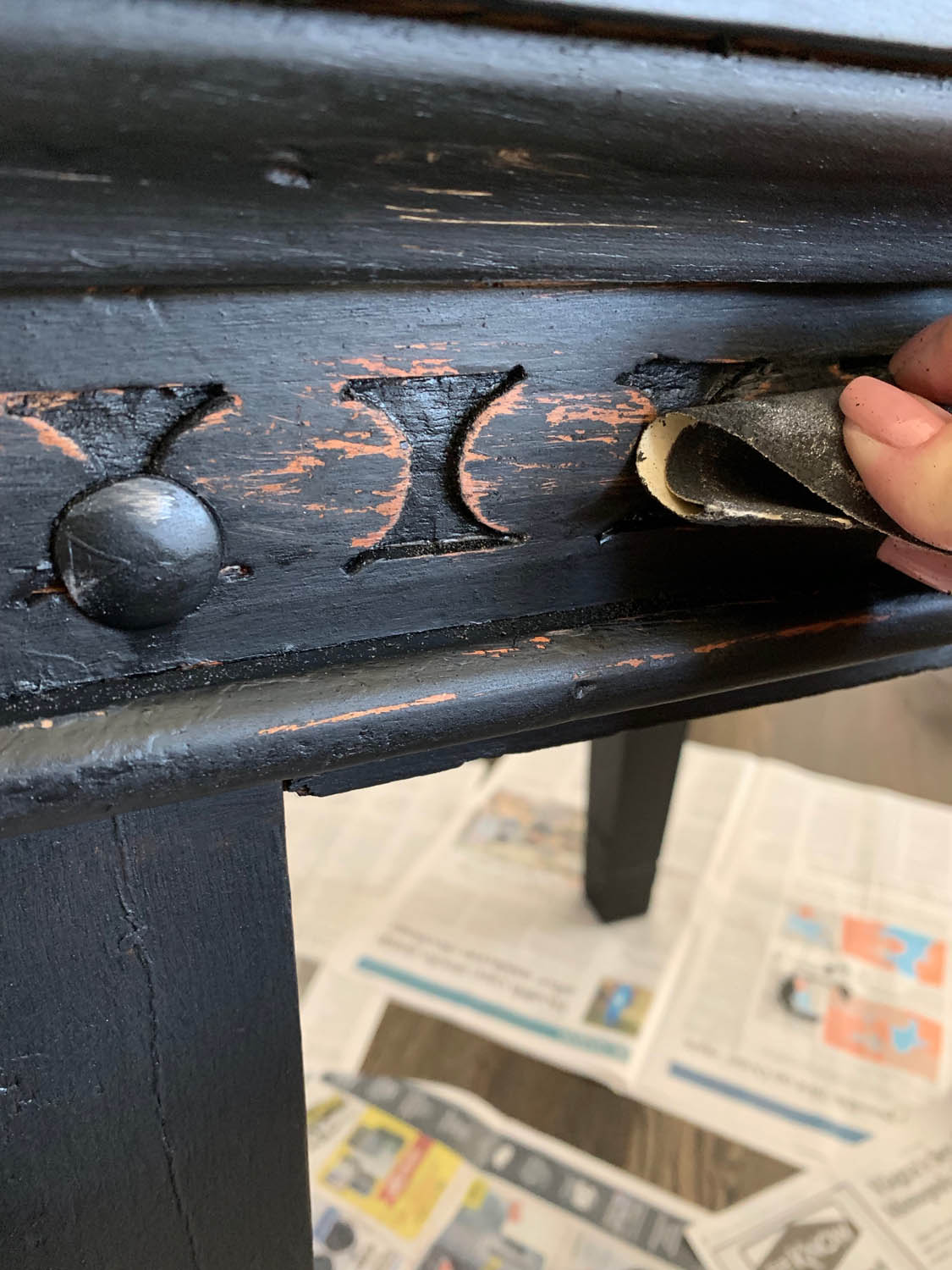distressing the black painted table with a piece of sandpaper