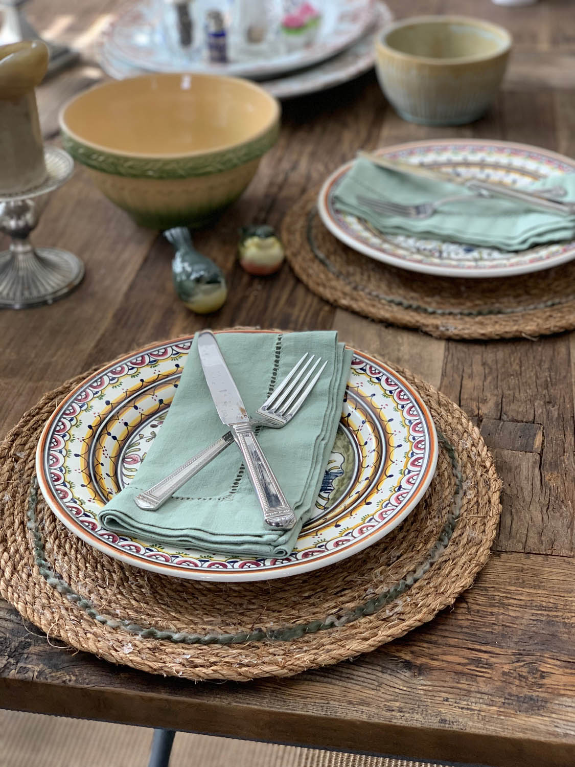 Farmhouse table setting with DIY rustic rope placemats on wood table with pottery, silverware and linen napkins.
