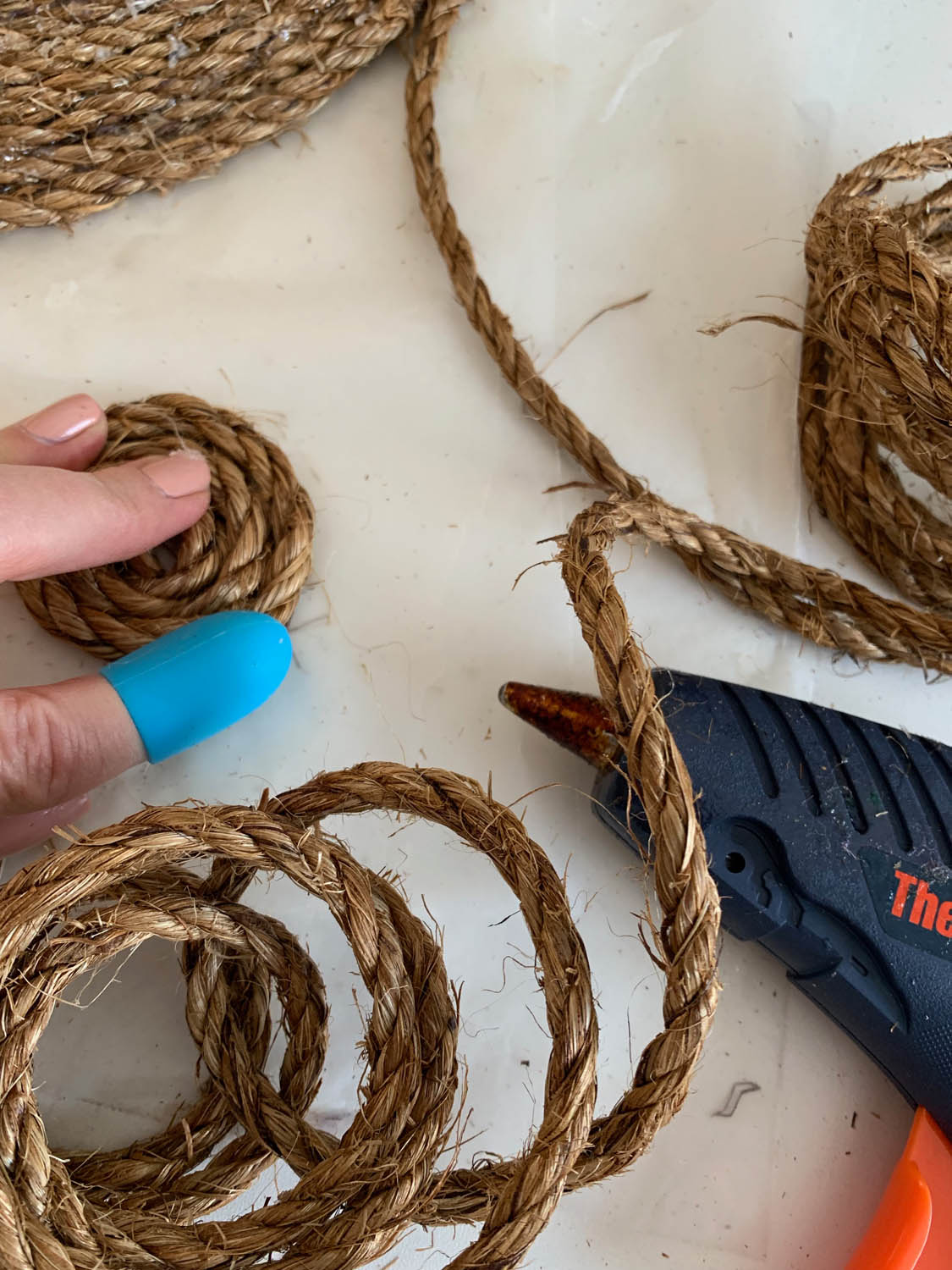 Fingers tightly coiling and hot gluing rope to make rustic rope placemat.