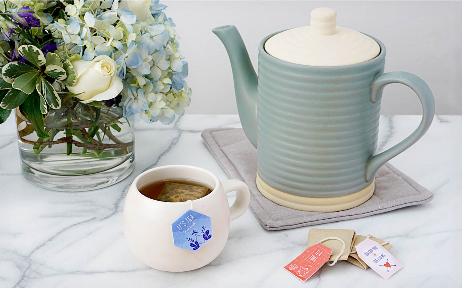Tea cup with custom print at home tags and DIY tea bags with tea pot and floral bouquet
