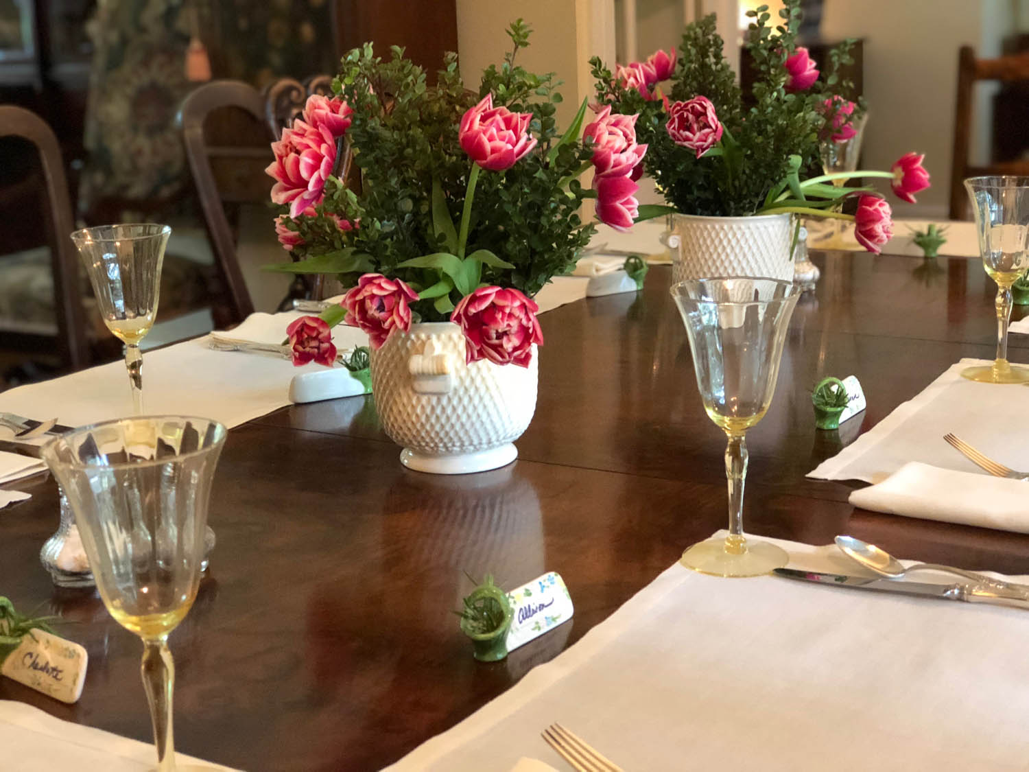 Simple elegant dining table setting with roses, goblets, and linen placemats