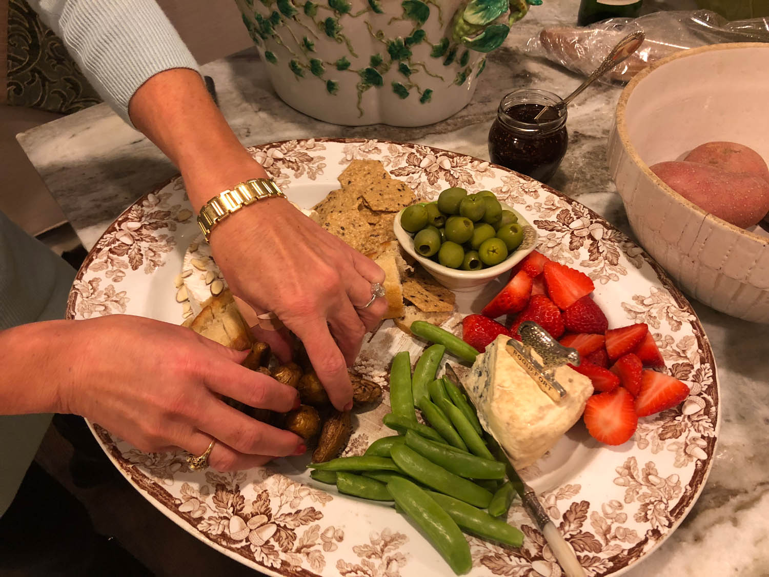 Host's hands arranging ingredients on hand on a pretty platter for quick and easy appetizers