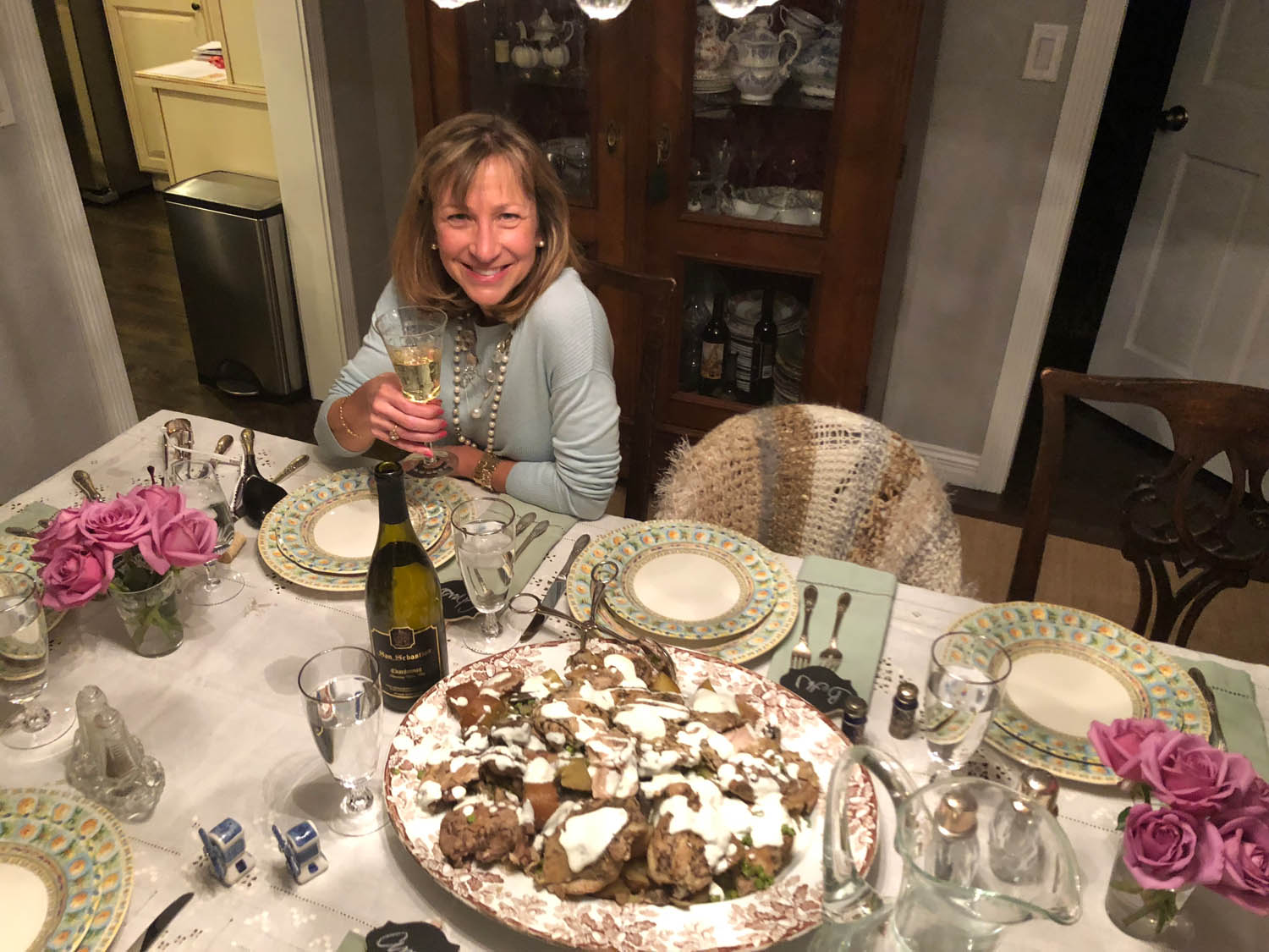 Hostess sitting at dinner party dining table with platter of chicken fricasse recipe