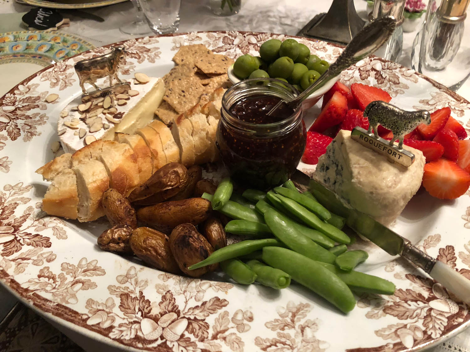 crusty bread, olives and other simple ingredients on hand served on a platter for appetizers