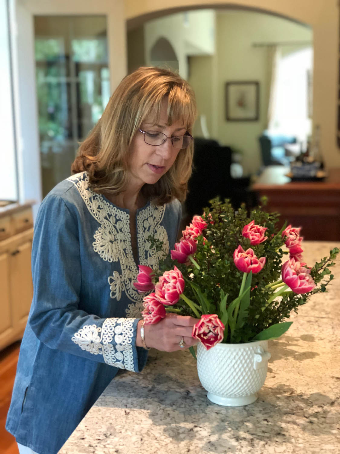 Ashley arranging tulips with boxwood cuttings in a vase