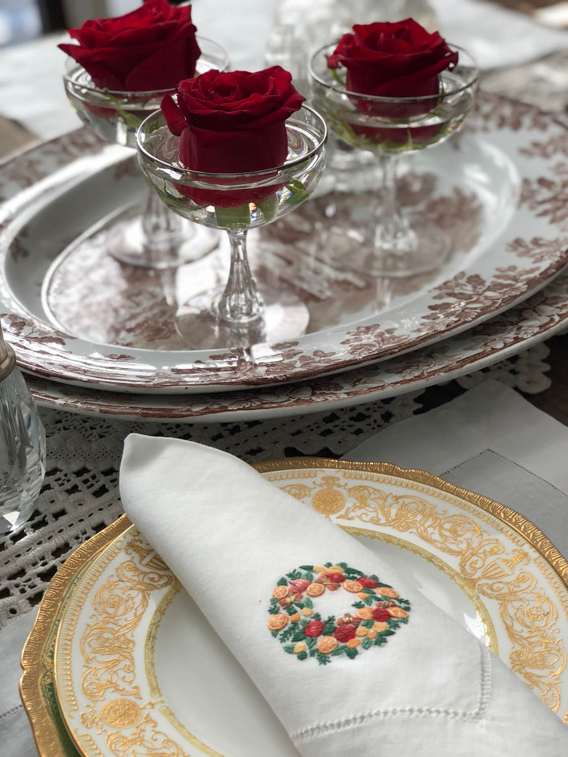 Red roses floated in goblets next to fine china and embroidered napkin