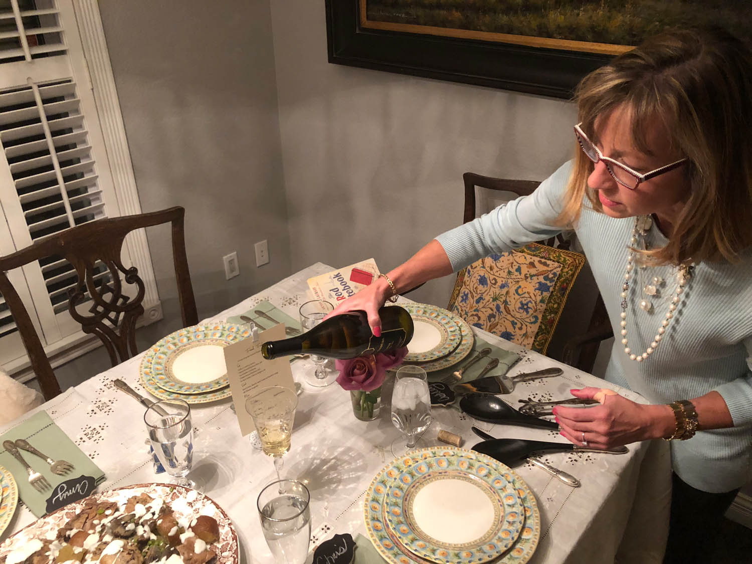 Ashley pouring wine into wine glasses at a dining table set with china