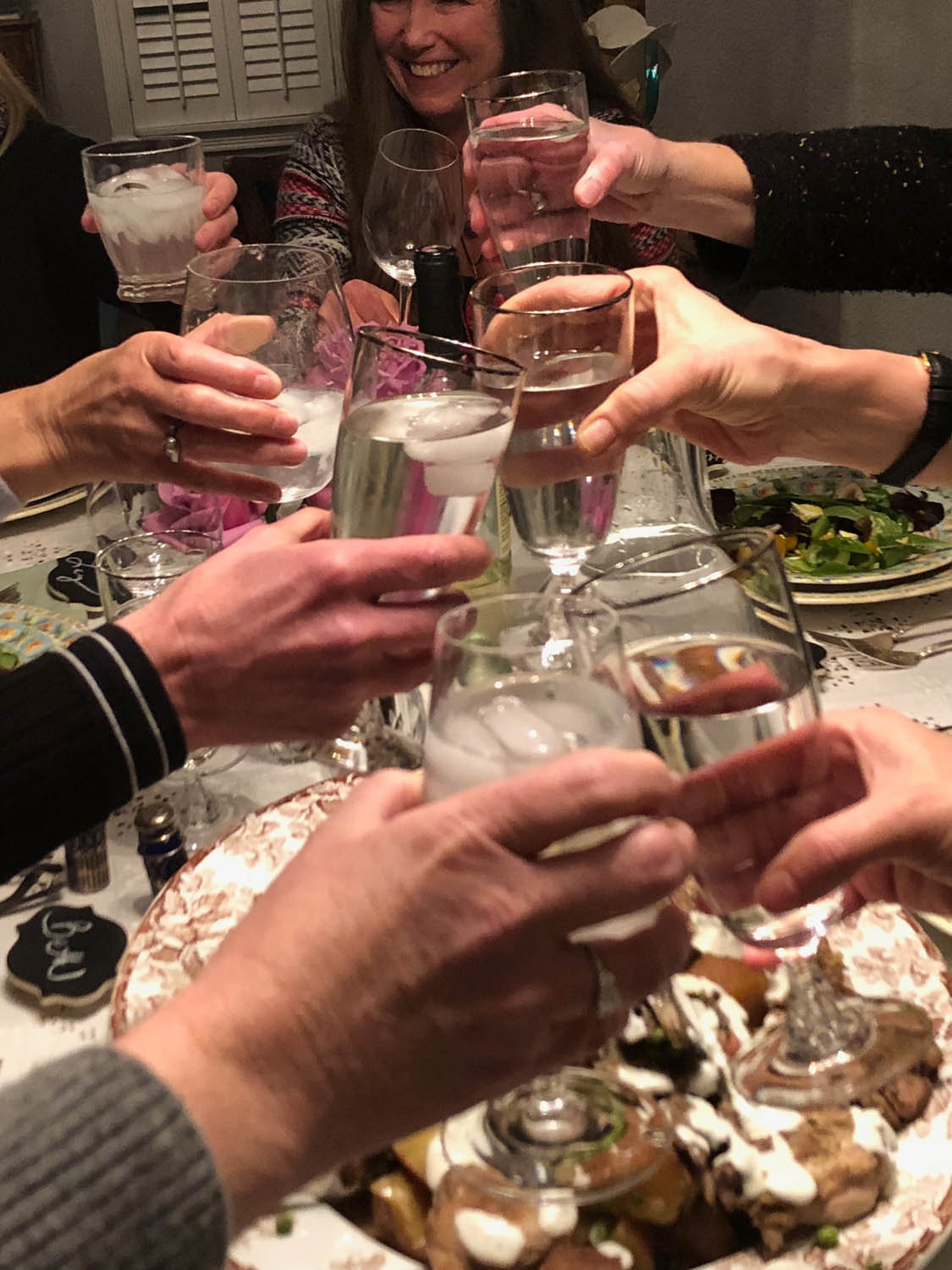 Ladies' hands toasting goblets over a shared dinner.