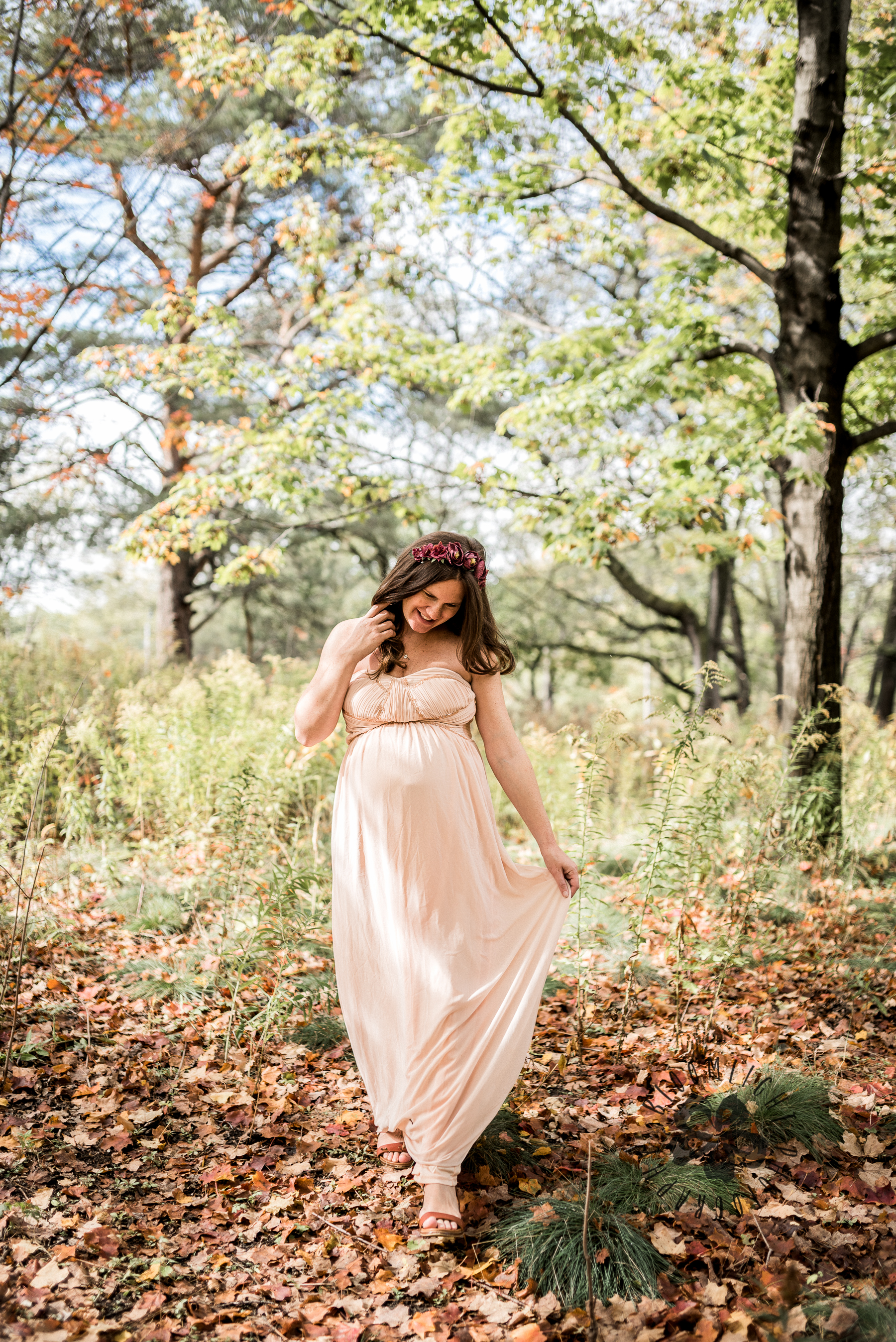Beautiful mamma to be in a blush long dress walking in High Park in Fall season.