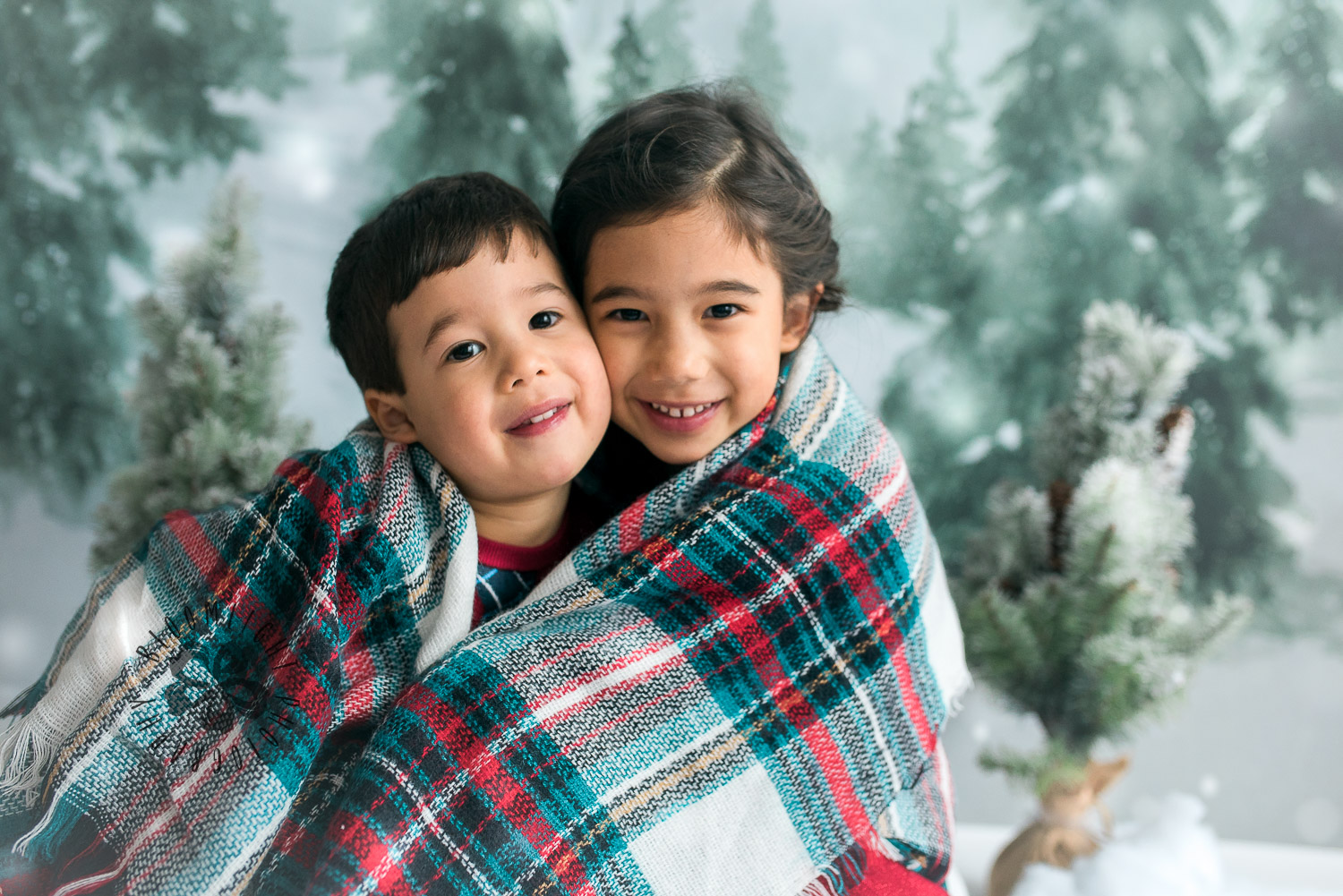 Siblings photo wrapped with a Christmas color blanket