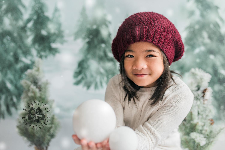 Lovely little girl holding snowball in her hands