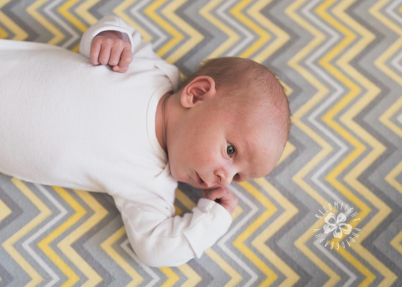 Newborn in his yellow and grey mattress