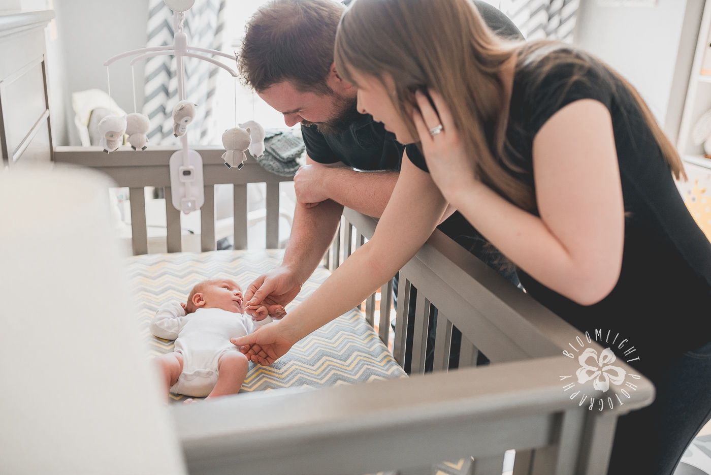 Family photos with their newborn in yellow and grey nursery