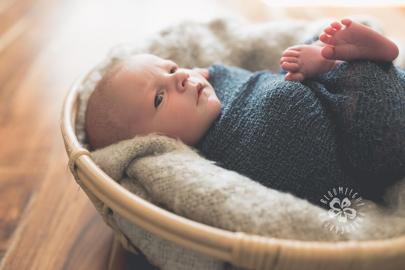 Baby newborn wrapped in dark grey in a wooden basket