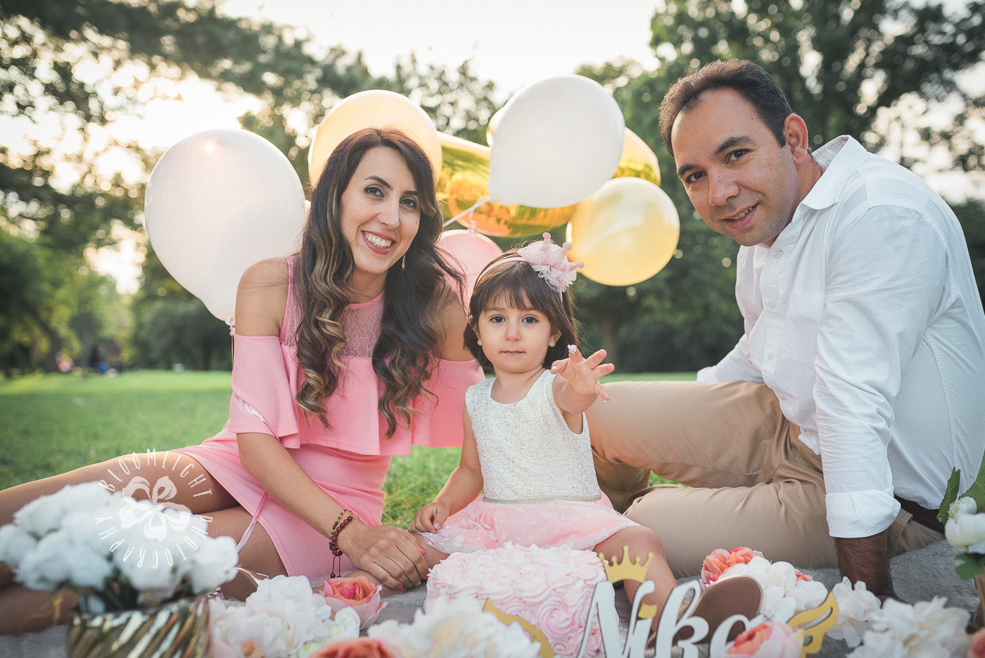 family of 3 sitting in a park in Toronto while celebrating 2nd birthday for their baby girl