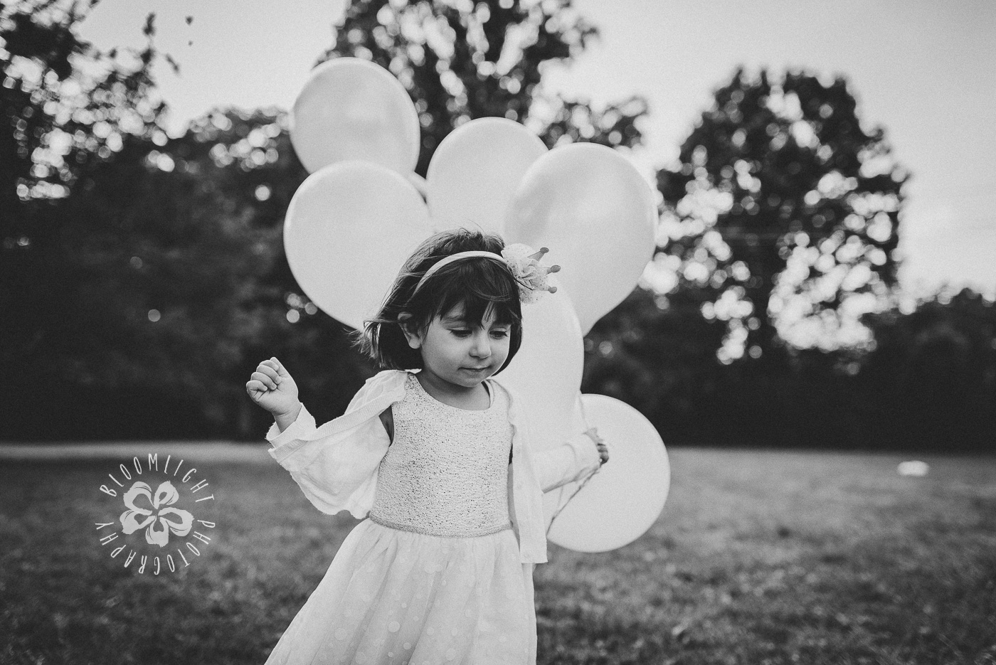 A toddler holding lots of balloons in her hand and running happily in a park in North York, Toronto