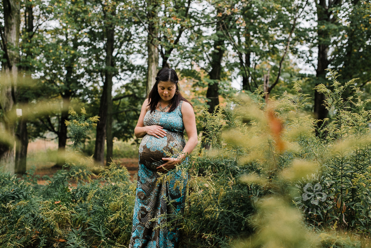 Pregnant mamma wearing patterned floral green and blue maxi dress, holding her belly bump, standing in green area, at High Park, Toronto.