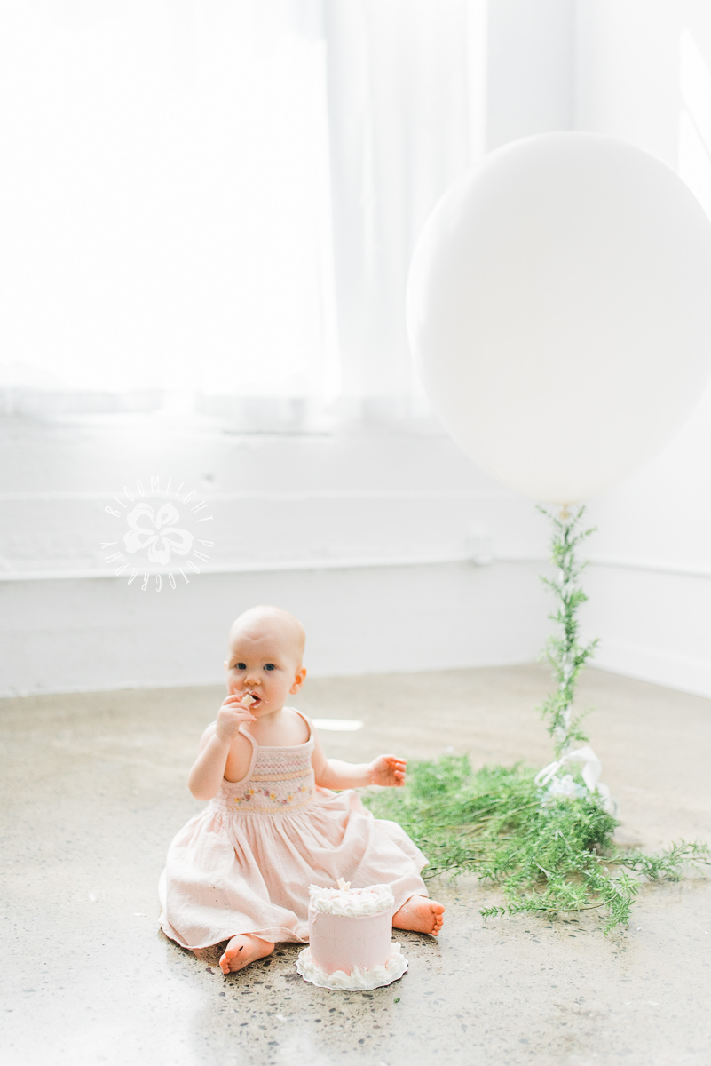 picture of baby sitting beside a big white balloon, having her first birthday cake