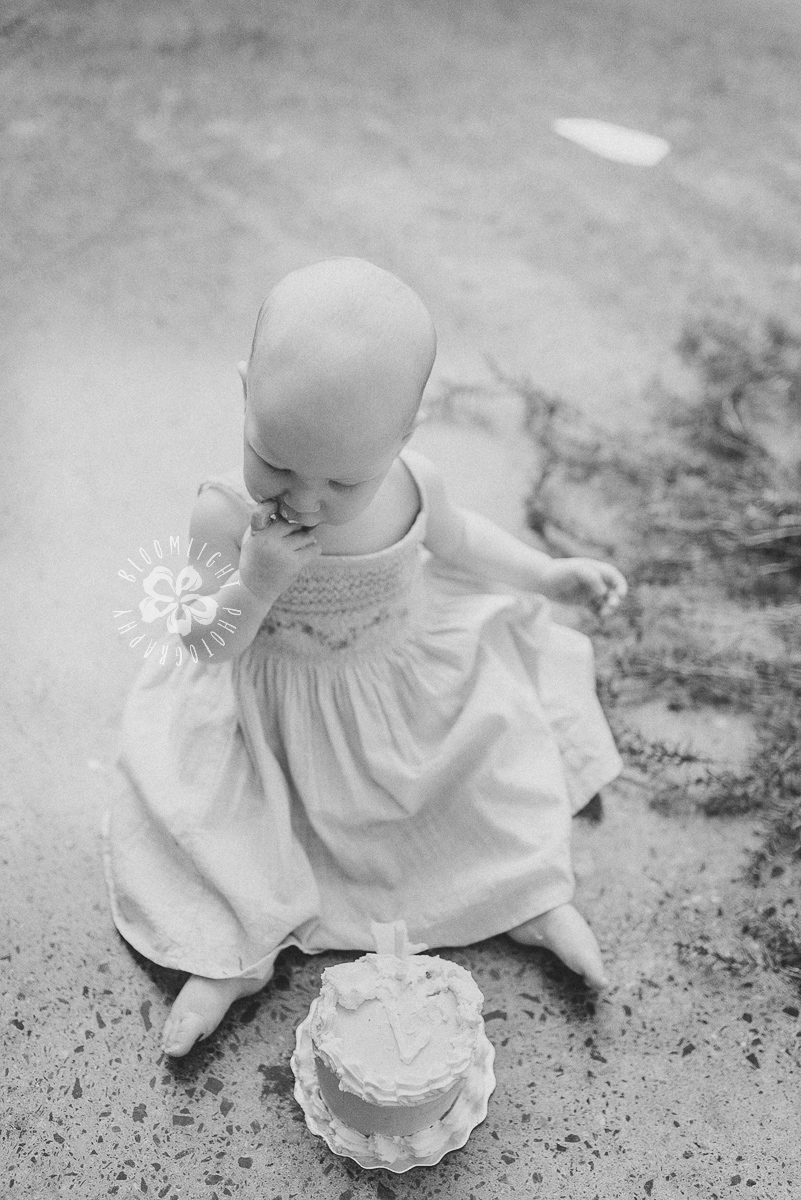 black and white photo of baby in her first cake smash session.