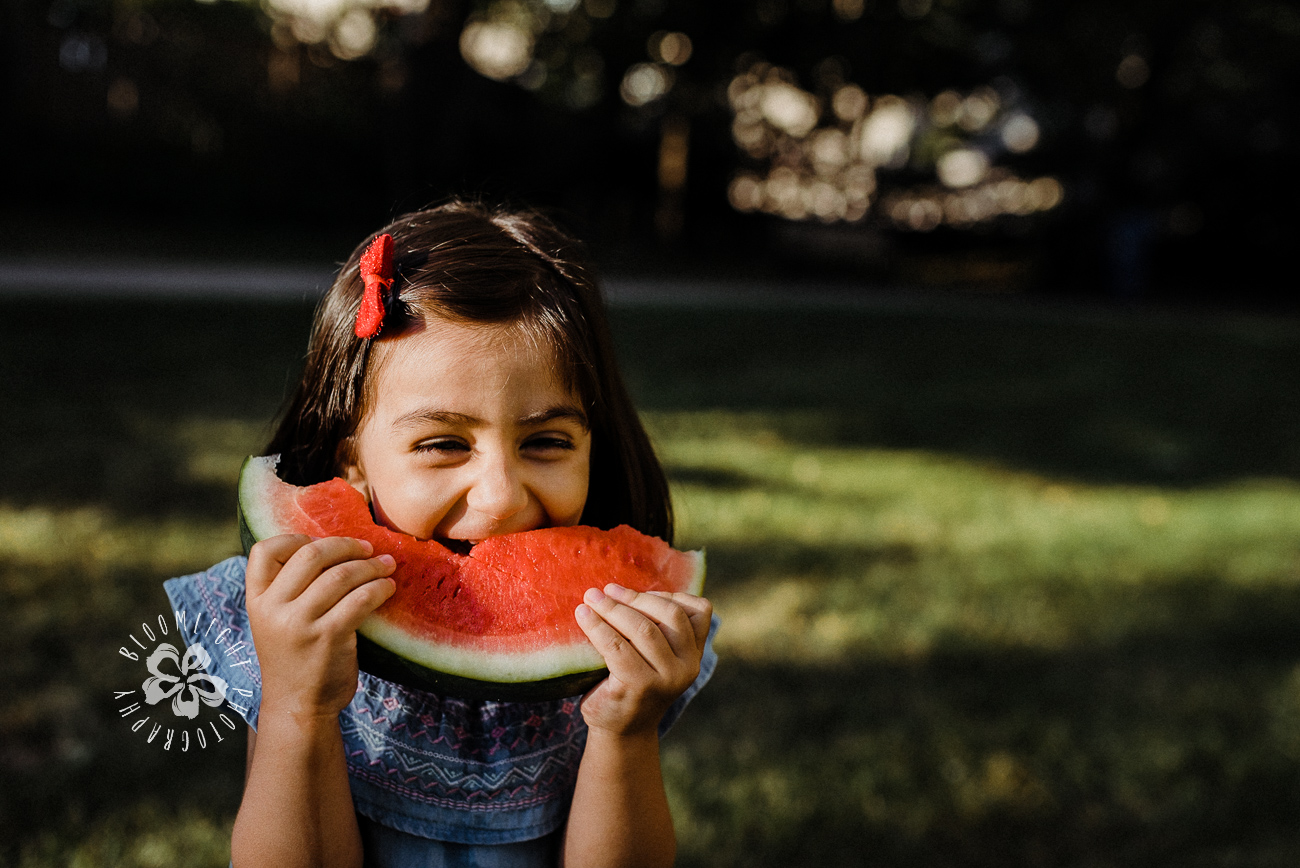 Little girl laughing and having a slice of watermelon in a park.