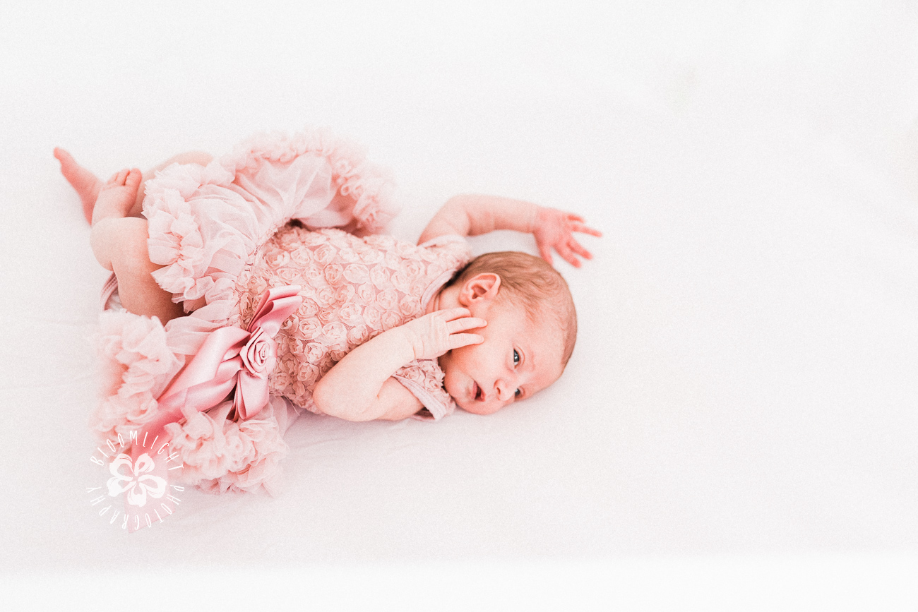 newborn wearing pink flowery dress
