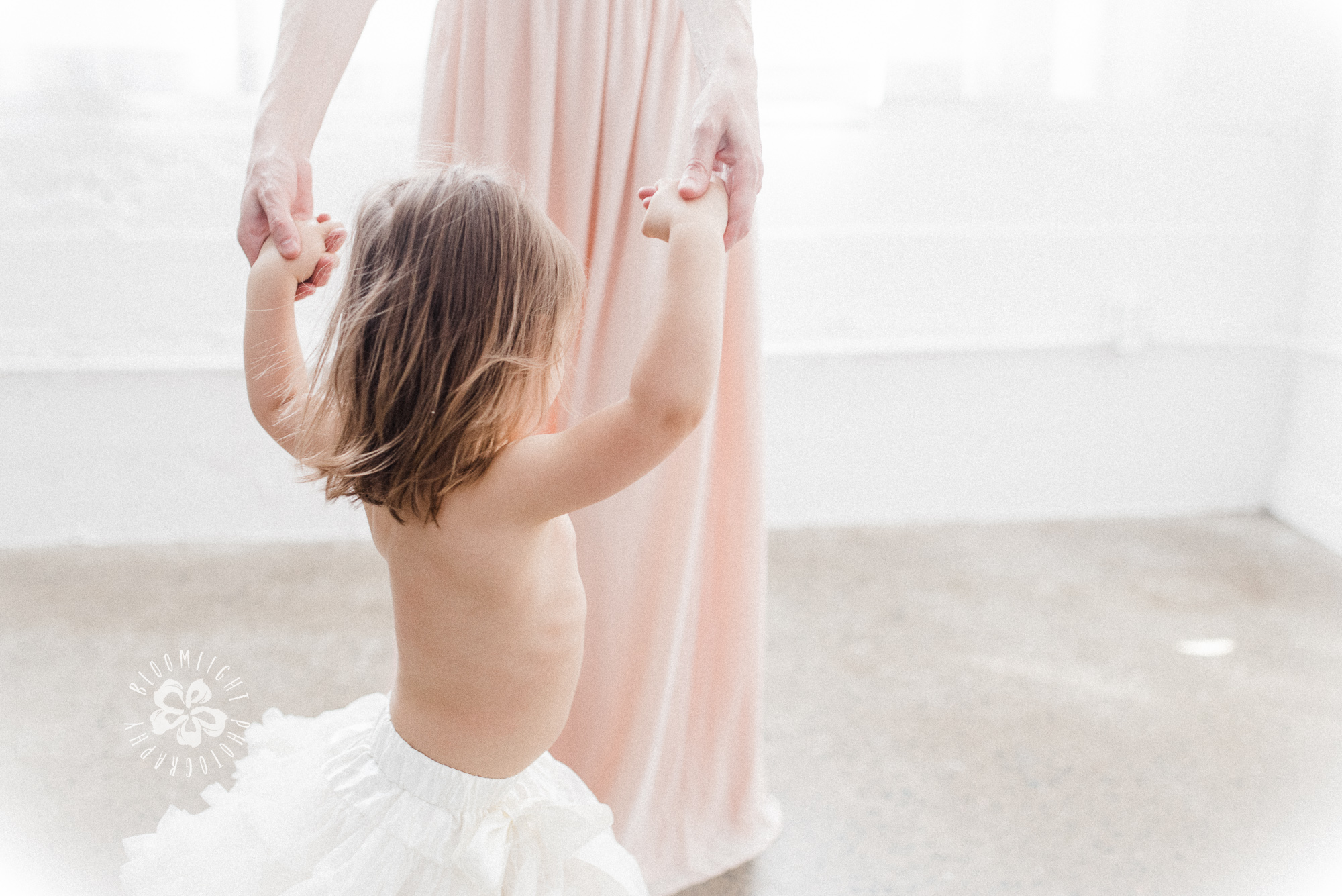 Photo of a baby girl dancing with her mom
