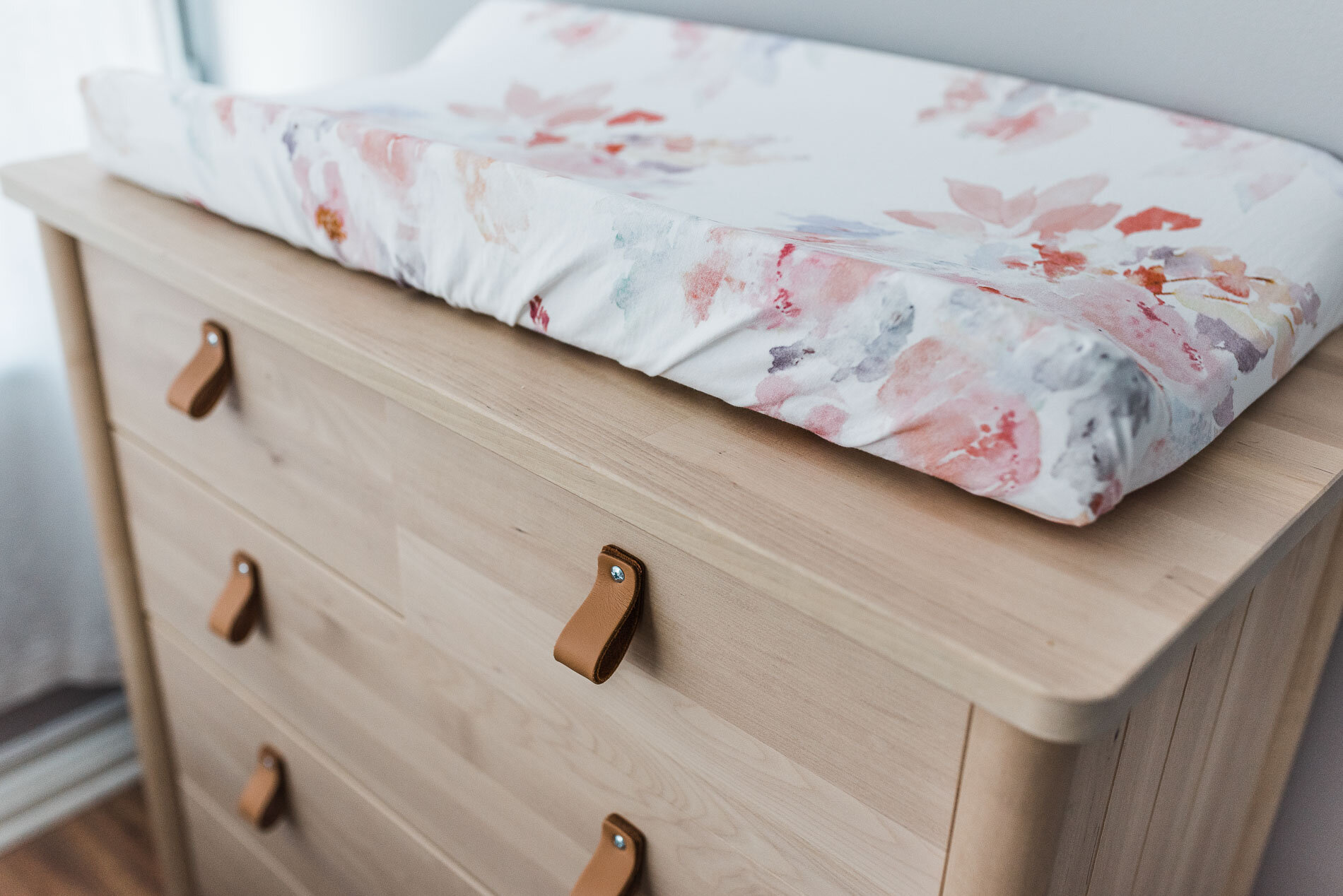 wooden baby nursery dresser and a changing pad
