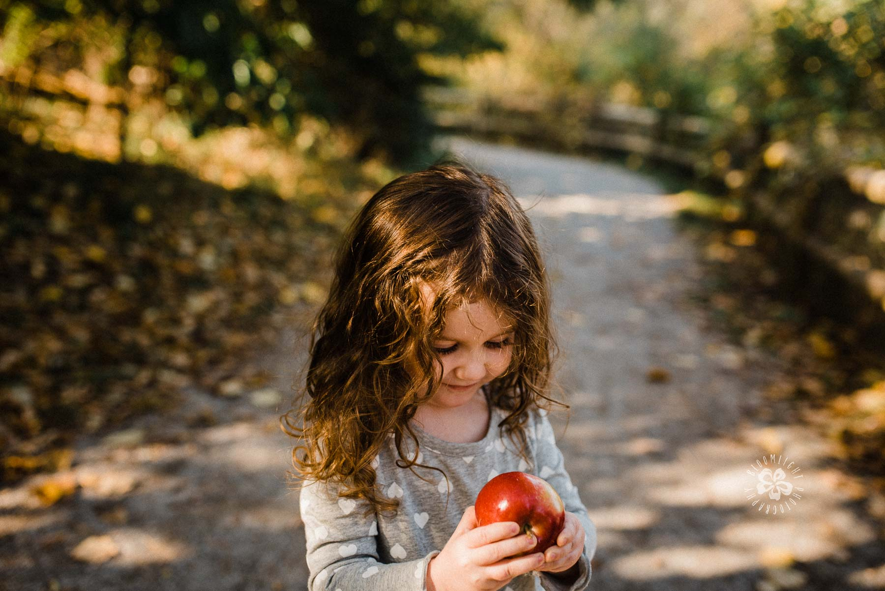 Sweet little girl looking at her apple in her hand while standing in a beautiful trail of Fall season