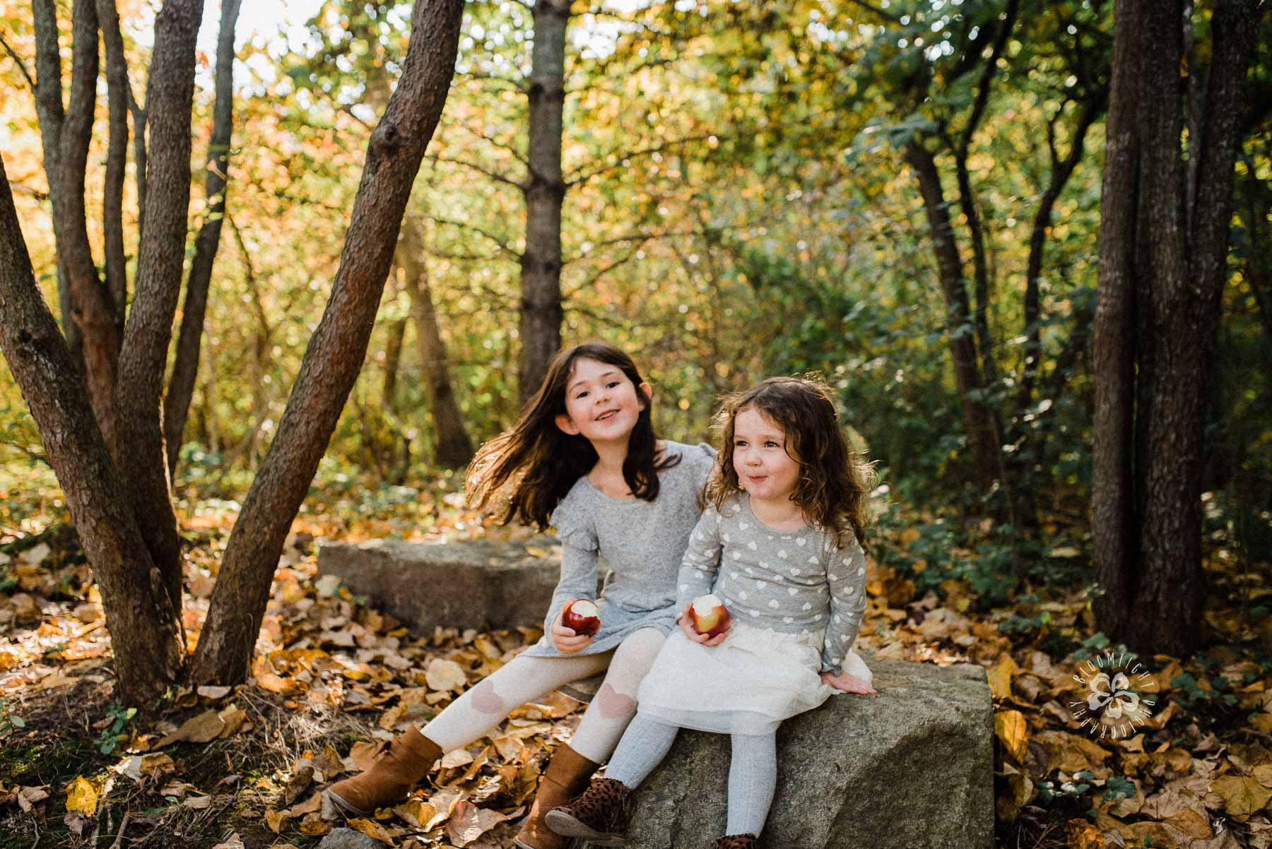 Sisters sitting on a rock in Evergreen Brick works park in Toronto in a colorful Fall.