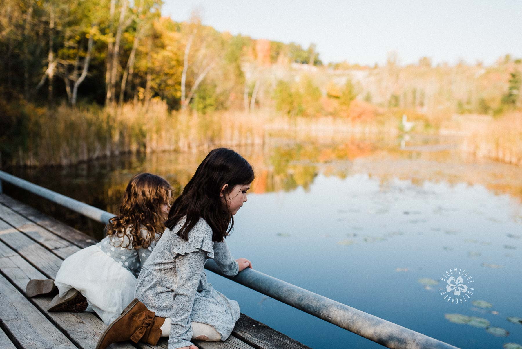 Two children sitting at the deck, looking at water and beautiful nature at Evergreen Brick works
