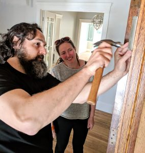 Rabbi Dan Ain and Alana Joblin Ain hanging a mezuzah on the doorpost of their new home in San Francisco