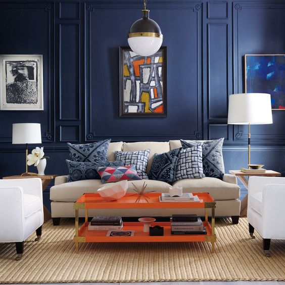 Blue and Orange: I did a project in school with these colors. Used in limited doses, these two colors love each other in a space. A neutral sofa and white side chairs add contrast. The seagrass area rug grounds the space and keeps it from becoming too formal. The wall moldings have a lot of detail which curbs the deep blue paint color and actually makes this room very appealing. Accessories and flowers for table top are the necessary details to ground this space. I love the floor lamp and contemporary art that finish off this space so beautifully!