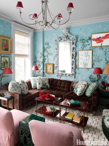 This is a charming family room done by Celerie Kembell. The Gracie wallpaper is always beautiful in this space. Pop's of red on the lamp shades are repeated in the art, cocktail table and side chairs. Brown, which is considered a neutral again grounds this space and keeps the design elegant and comfortable.