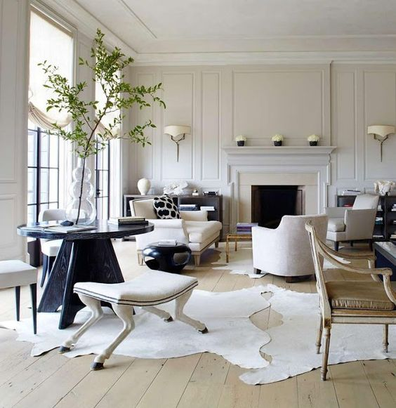 A beautiful achromatic designed room with many layers. Wood floors, furniture covered in soft textural fabrics. Millwork, drapes, plants and accessories add touches that make this room cozy and comfortable.