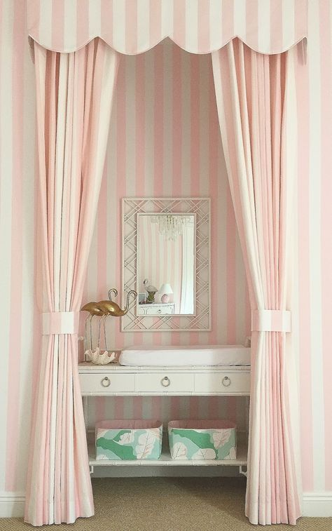 This vignette is very creative and functional at the same time. It is really a dresser that has been used as a changing station and storage. The framing out of this nook with the striped drapes and valance make this space fun and inviting!