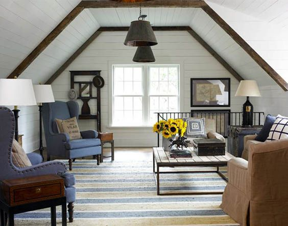 Wood beams, ship lap, wood cocktail and side table along with warm colored fabrics on the sofa and pillows make this space inviting. Even the blue wing chairs are warm because of the the matte, nubby fabric on them.