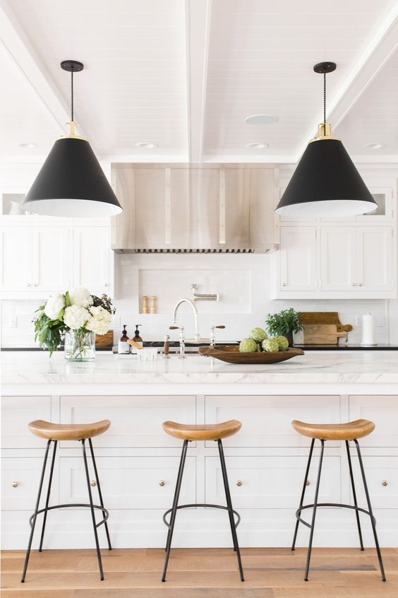 Love the simplicity of this kitchen with the white carrera counter tops, black pendant lights and wood barstools. A tip for more storage is to have cabinetry under the center counter in front of the bar seating. This can either be hidden or shown with knobs like this photo.