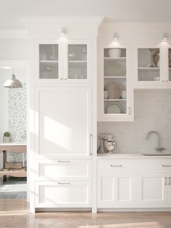 Covering a refrigerator with millwork is one of my favorite design specifications.  I personally feel that too much steel in a room with all the other appliances will take away the beauty and warmth of a white kitchen.